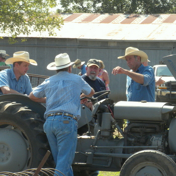 Williamson County area farmers discuss farming around a tractor.