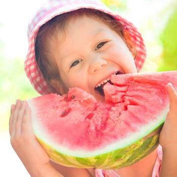 Little girl eating watermelon.